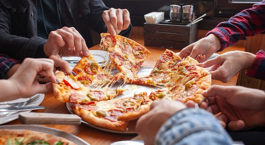 people holding pizza slices